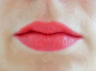 Arbonne Smoothed Over Lipstick swatch on lips in Poppy