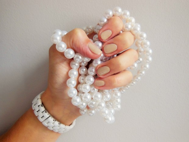Nude manicure featuring pearl necklace