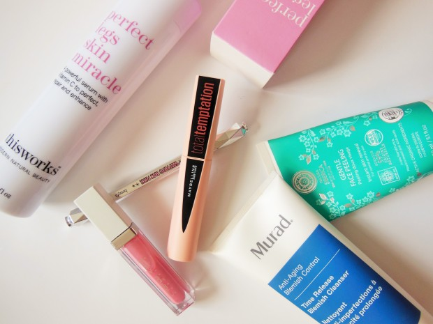 Beauty products flatlay including lipgloss, mascara, cleansers
