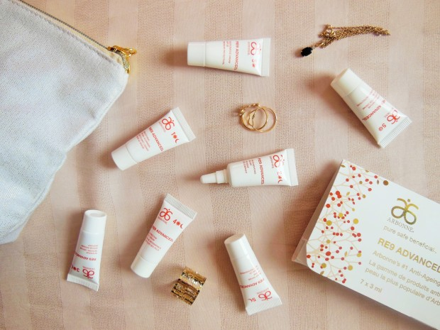 Arbonne RE9 Advanced skincare mini tubes flatlay on a stripy beige background