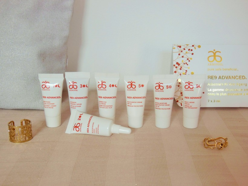 Arbonne RE9 Advanced skincare mini tubes in a row on a beige background