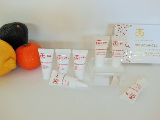 Arbonne RE9 Advanced anti-ageing mini tubes on white background with fruit