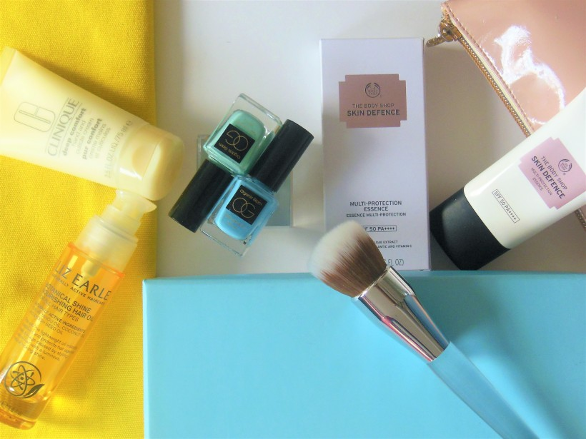 Beauty flatlay featuring tubes, bottles and brush