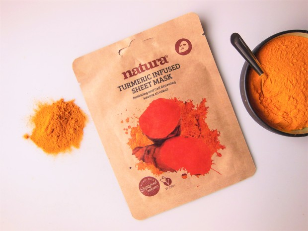 Turmeric sheet mask with turmeric powder in a bowl