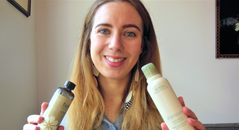 woman holding a bottle of body oil and a bottle of body lotion