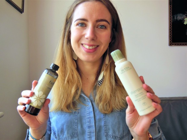 Woman holding bottles of body cream and body oil