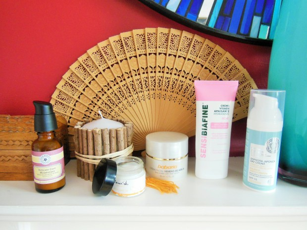 Face creams on shelf with wooden fan