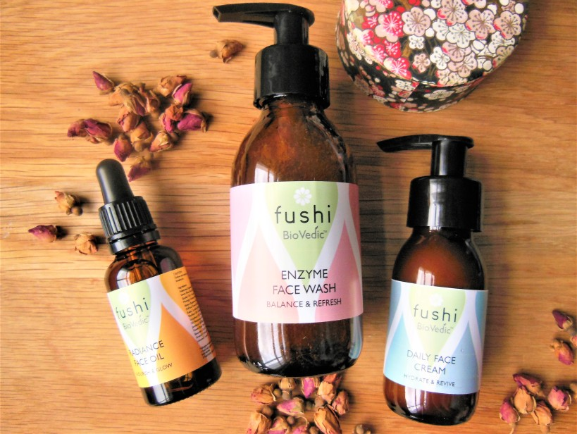 Three natural skincare products with rose buds on a wooden background