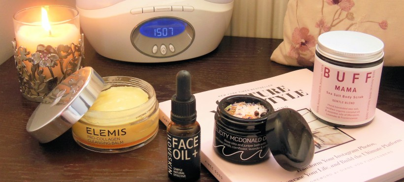 Beauty products on a bedside table with burning candle