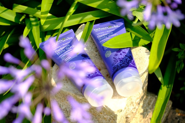 Two purple skincare tubes lying down on a rock