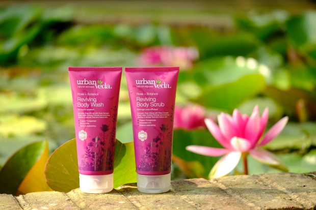 Two dark pink skincare tubes on a brick wall
