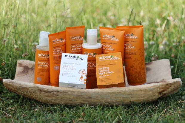 Skincare range on a wooden tray in the grass
