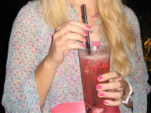 Woman with pink manicure holding drink