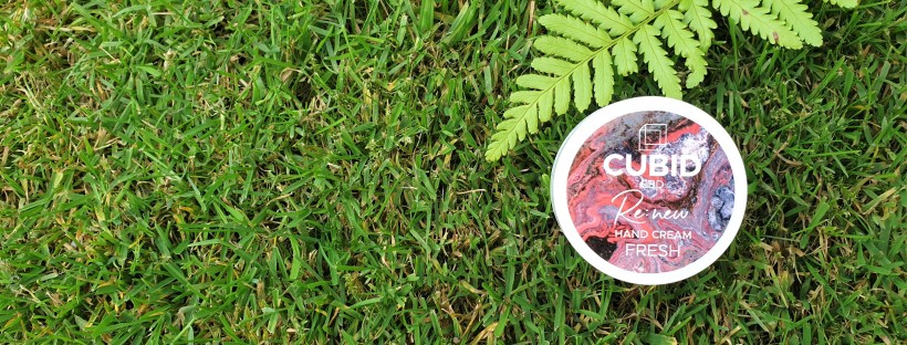 Mini pot of hand cream on grass background