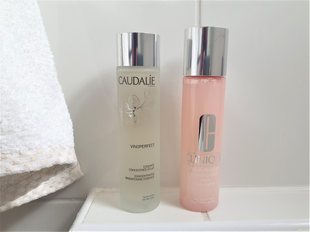 Two skincare bottles in a white bathroom