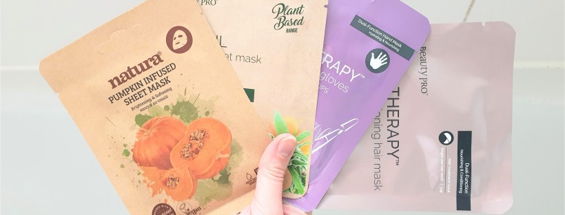 Hand holding four sheet masks